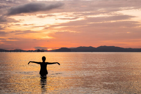 sillhouette: woman relaxing and exercise in sunset at  sea Stock Photo