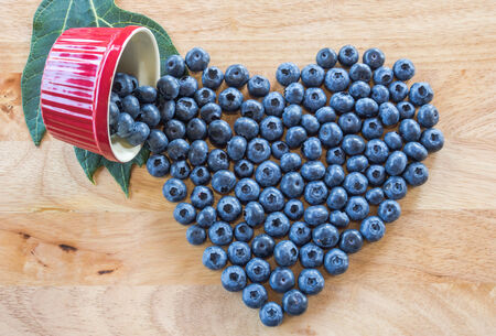 Heart from fresh blueberries on wooden table