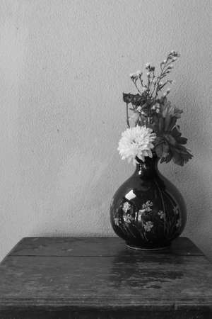 Still life with flower on wooden table on black and white photo