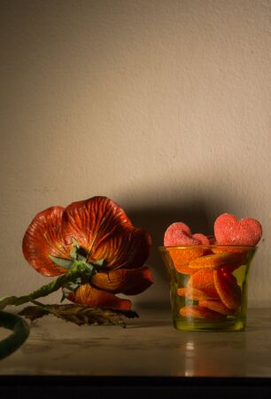 Still life with flower and jelly heart  in yellow glass