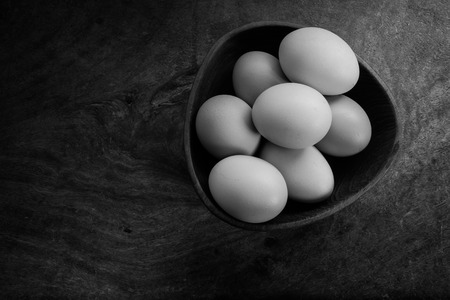 antique dishes: still life with eggs and grunge background on black and white