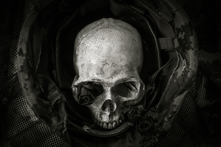Still life with human skull in soldier helmet