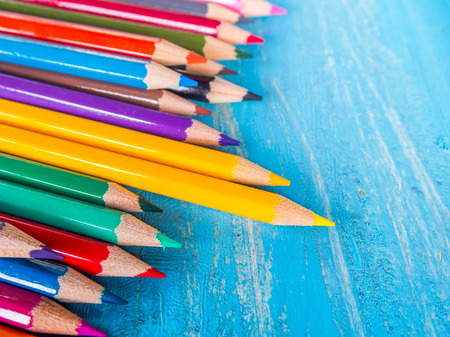 Row of colorful pencils on wooden background