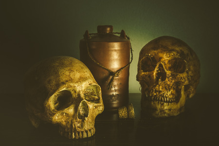 Still life with human skull and bottle of alcohol on vintage background Stock Photo