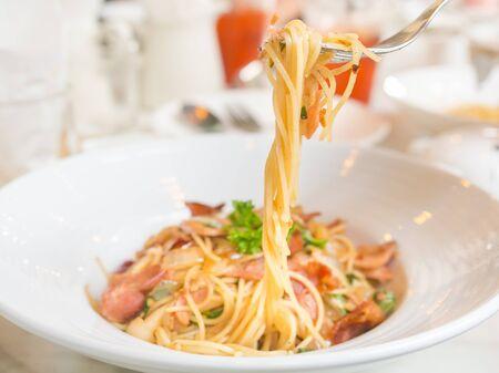 Spagetti gebakken met spek en gemengde groenten op een witte plaat Stockfoto