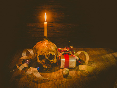Still life with gifts ,human skull and candle light on dark background