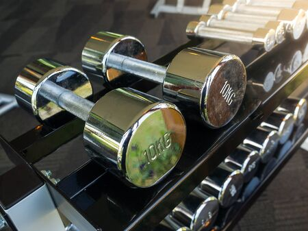 Row of heavy dumbbells in sport gym for strong healthy