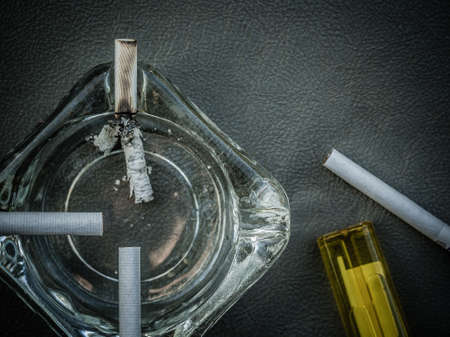 encendedores: White cigarettes and clear ashtray on leather background