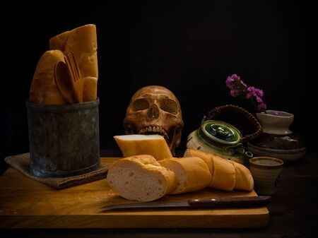 Still life with human skull and food on wooden background Stock Photo