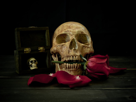 Still life with human skull and red rose on wooden background
