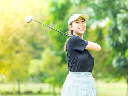 Asian cute woman smiling after end of swinging golf club Stock Photo