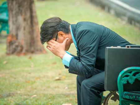 Business man sitting in outdoors park and stressed because of business work failure Banque d'images