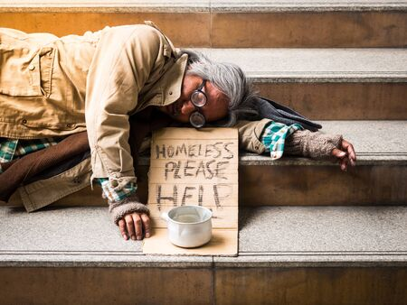 A poor homeless man sleep on a ladder with a donation bill