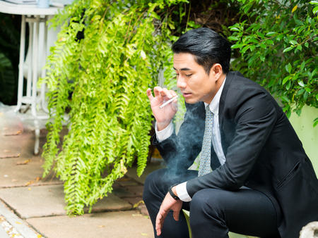 Young businessman smoking and thinking about business issues 版權商用圖片