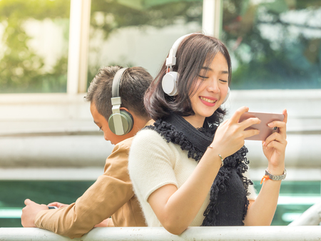 Young boy and girl play games and listen to music on their mobile phones