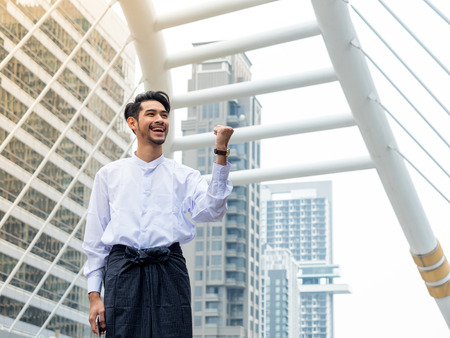 Young Burmese businessman happy after using mobile phone to find a data for his business 스톡 콘텐츠
