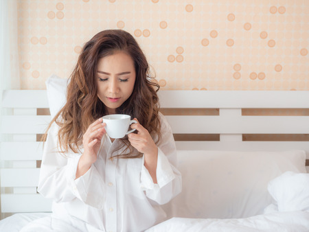 Beautiful woman is drinking coffee on the bed. After waking from sleep Stockfoto