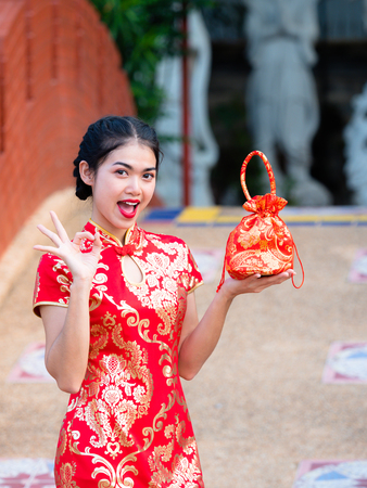 Asian women in Chinese national costumes hold greeting bag for the Chinese New Year event