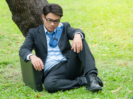 Business man sitting in outdoors park and stressed because of business work failure