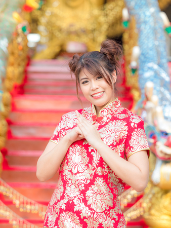 A beautiful Asian girl in a Chinese national costume raises his hands to bow Banco de Imagens