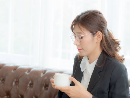 Asian business women use relaxed thoughts During the break for hot coffee after working hard in a highly competitive business