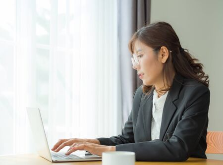 Asian business women are using ideas. And search for business information with a laptop computer