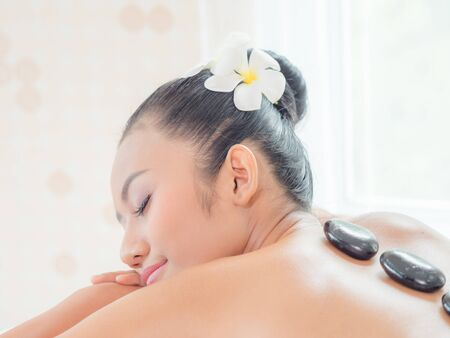 A beautiful Asian woman is relaxing in a spa shop when an expert masseuse places a hot stone on her back