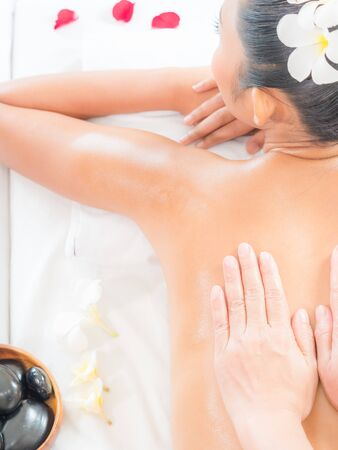 An expert masseuse at a spa salon puts her hands on the back of an Asian woman to relieve tension from work Stok Fotoğraf