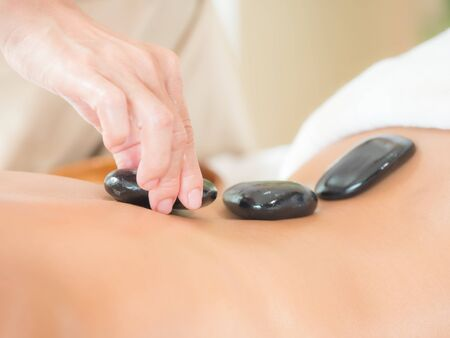 An expert masseuse at a spa salon puts hot stone on the back of an Asian woman to relieve tension from work