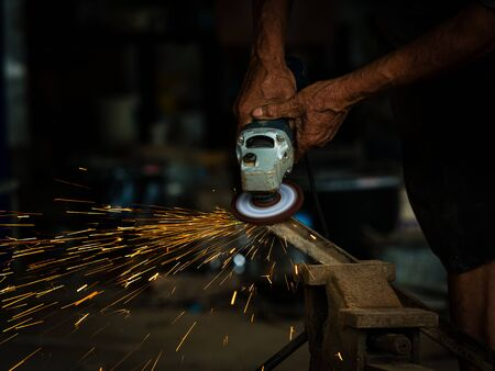 Professional technicians in the factory are using power tools to polish the metal to cause sparks, To be used in assembling with other work pieces