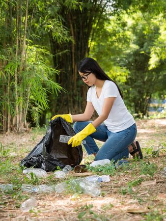 Volunteer women collect plastic water bottles in the park area, From people who refuse to throw in the trash into plastic bags for recycling Stock Photo