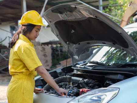 The woman in the mechanic's uniform is opening the radiator cap of the engine to check the water level, In accordance with engine maintenance standards