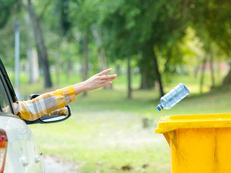 The woman threw a plastic water bottle after drinking all the water into the prepared trash for storage for recycling