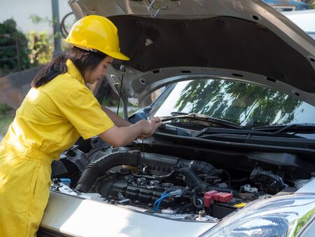 Women in work uniforms are measuring car engine oil levels, Which is according to the standard of engine maintenance