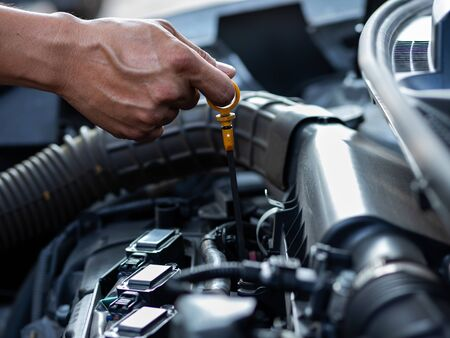 The mechanic's hand is measuring the engine oil level, Which is according to the standard of engine maintenance Foto de archivo
