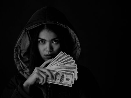 A young woman shows a lot of the money she earned from using methods to search for information and use it illegally