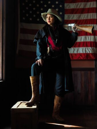 A Western cowgirl is preparing to use a gun to defend herself in a land where people must protect themselves, Since it was an era where the law had not yet been reached