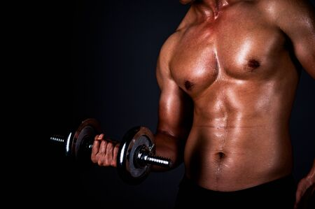 The strong Asian man lifted his dumbbell regularly to keep his muscles strong and beautiful 写真素材