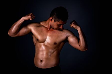 A strong Asian man raised his arms to show his strong and beautiful muscles from exercise to build muscle in a fitness center