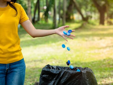 The woman threw the bottle cap after use into the trash prepared for storage for recycling and reuse, To help reduce global warming