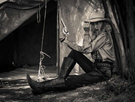 A young cowgirl sat with a gun to guard the safety of the camp in the western area