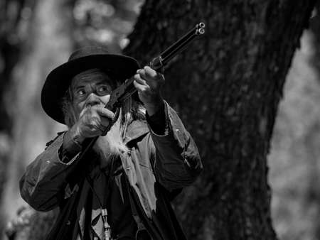 A senior cowboy is aiming the rifle at the attacker, While security surveillance in rural farm areas