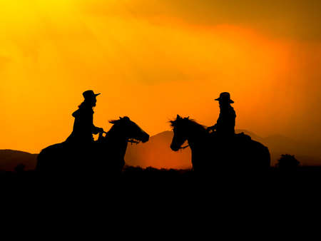 The Western Cowboy forced his horses to stop while the sun was setting, In lands where the law has not yet reached 写真素材