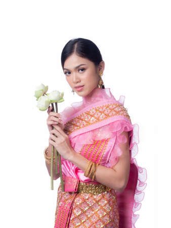 A charming Thai woman in ancient Thai dress holding a lotus flower that is used for worshiping religious monks for the Loy Krathong Festival in Thailand