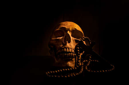 Still life art of a human skull and bead on a black background