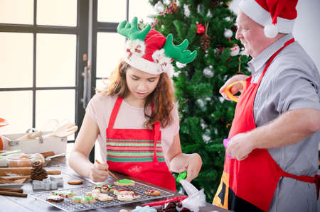 A European girl and her father are wearing gingerbread paint makeup that she finishes for Christmas and New Year