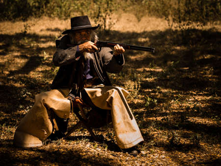 A senior cowboy sat with a gun to guard the safety of the camp in the western area
