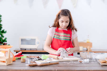 European girls prepare tools and ingredients for making gingerbread during Christmas and New Year celebrations