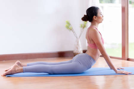 Asian women meditation and stretching relax their muscles by doing yoga in the room Фото со стока