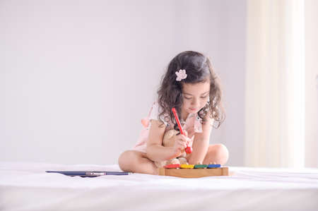 A cute young Asian girl was happily playing a wooden toy instrument in the bedroom
